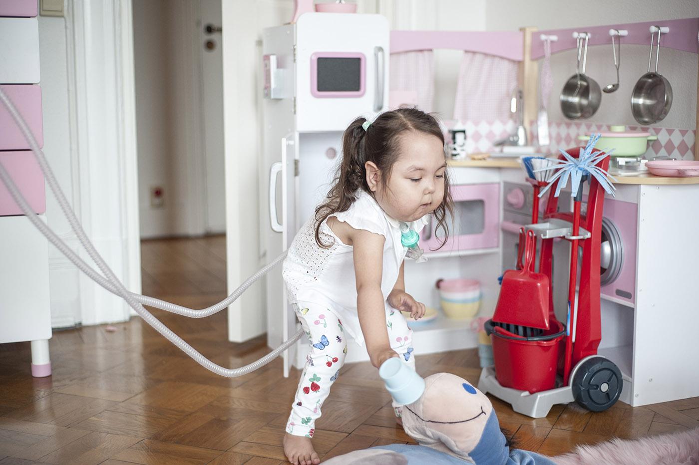 Den smidiga lilla hemventilatorn som låter barnet delvis styra andningen själv var Alisa Johansson först i Skandinavien med att få prova. Äter gör hon via en knapp på magen. Foto:  Li Fernstedt