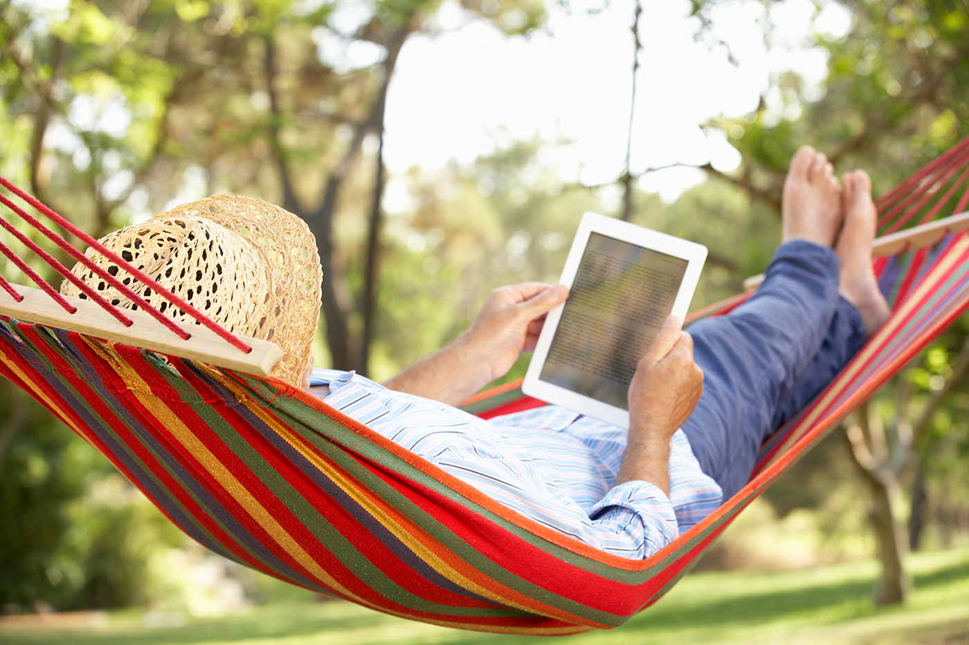 Man wearing hat relaxing in hammock with e-book